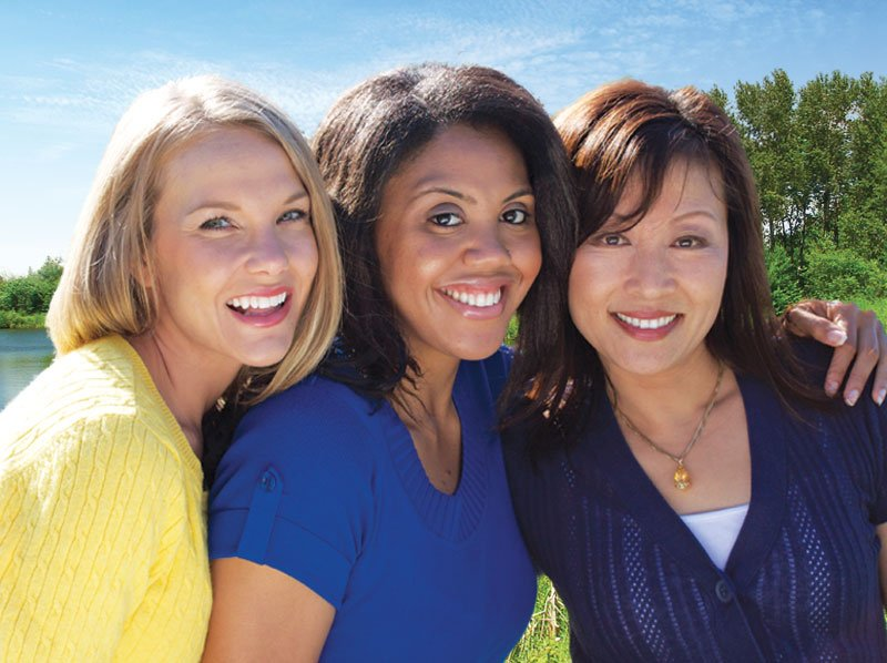 Three woman standing side by side smiling